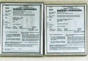 本報記者前日到特區清潔商協會位於觀塘京貿中心登記地址,門牌為真會記有限公司,往內看,辦公室牆上掛「特區清潔商協會有限公司」(左)及「真會記有限公司」(右)商業登記文件,但在內職員否認該處為特區清潔商協會。(鄧宗弘攝)