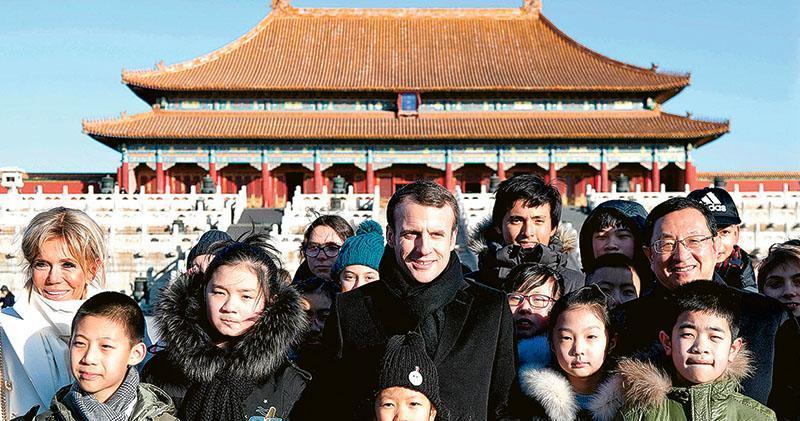 正在訪華的法國總統馬克龍偕妻子布麗吉特(左一),昨日上午參觀北京故宮,並在太和殿前與中法兩國的小朋友合影。(法新社)