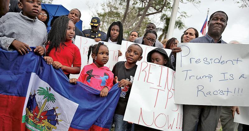 前日是海地大地震8周年紀念,美國邁亞密有民眾出席紀念儀式,同時展示標語指摘總統特朗普是種族主義者,反對他據報以「糞坑」侮辱海地、非洲和薩爾瓦多等國。(法新社)