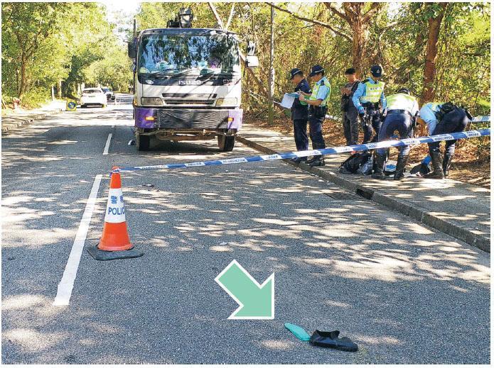老翁橫過沙頭角公路被私家車(左)撞飛至對行線,復遭駛至中型貨車(右)撞中重傷昏迷,送院不治。警方封鎖現場調查,馬路遺下死者一隻鞋(箭嘴示)。(衛永康攝)
