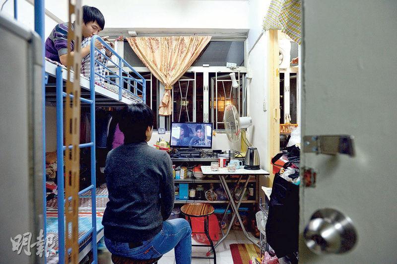 李女士(中)與兒子(左上)新遷的劏房面積約90呎,由於單位沒接駁電視天線,月租減至3600元,若以呎租計算,仍較以前租住的單位貴三分之一。圖中李女士透過電腦看電視劇集。(鄧宗弘攝)
