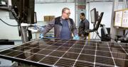 美國政府周一宣布,向進口太陽能板及洗衣機徵重稅,對中韓影響較大。圖為美國俄勒岡州一名操作員上周在廠房檢查太陽能板。(路透社)