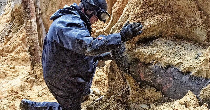 警方爆炸品處課的拆彈專家昨午走近視察新發現的千磅戰時美軍空投炸彈,相信與上周六發現的屬同一類型。拆彈專家指昨日天雨致泥土鬆脫,增加拆彈難度,預計所需時間較上次26小時更長。(警方提供)