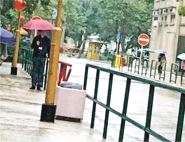 大埔浸信會公立學校副校長吳滿堂被影到企喺校外撐傘護送學生入校,佢話噚日「的確有好幾位小朋友沒有帶雨具,所以都會特別擔心他們,尤其是天氣如此寒冷」。(網上圖片)