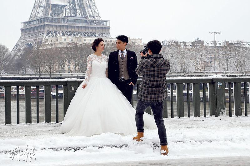 巴黎昨日下雪後一片白茫茫,一對新人在艾菲爾鐵塔前拍婚照。(路透社)