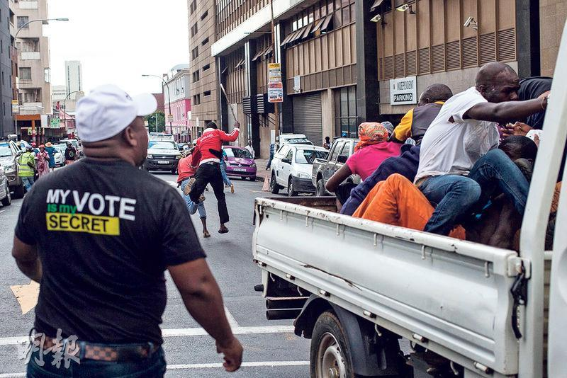 南非執政黨「非洲國民大會」(ANC)高層將開會商定現總統祖馬的去留。在約翰內斯堡的ANC總部,周一有ANC黨員持棍追打坐在貨車的「黑人土地優先」(Black Land First,BLF)運動成員。BLF支持祖馬,認為他應留任至總統任期明年完結,並指摘ANC企圖政變。(法新社)