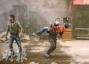 有敘利亞民兵組織人員周三在東古塔地區抱起一名受傷孩子,離開被政府軍空襲的現場。(法新社)