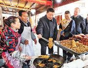 習近平前日在四川汶川縣映秀鎮考察時,在村民開辦的飯店體驗炸酥肉。(新華社)