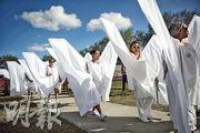 佛州馬喬麗斯通曼道格拉斯高中周日開放讓師生重返校園,為槍擊案後復課做準備。有17人打扮成天使到校園外的臨時悼念所,悼念17名死難者。(法新社)