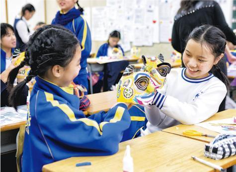 西九日前趁香港真光中學小學部舉行每年一度「文化活動日」,到校教導小四至小六生以摺紙方式製作立體獅頭,冀打破戲曲予人沉悶、古老的傳統感覺,推廣戲曲教育,配合年底戲曲中心開幕。(西九文化區管理局提供)