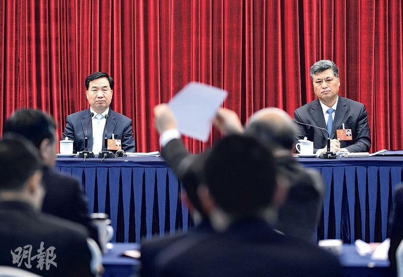 廣東省委書記李希(左)與省長馬興瑞(右)昨日於廣東團參與政府工作報告審議時,有代表向他們展示紙條。(中新社)