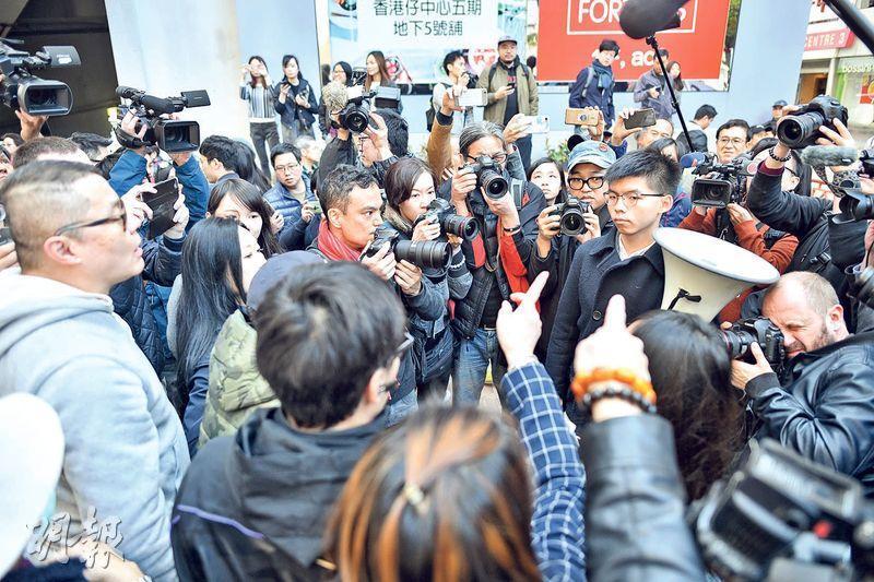 區諾軒(不在鏡頭)與競選團隊昨早到香港仔中心對出拉票,其義工被數名男子指罵、推撞,區認為對方為建制支持者。為他助選的香港眾志黃之鋒亦被包圍(圖),遭對方指罵是「漢奸」、「走狗」及以粗言侮辱。(蘇智鑫攝)