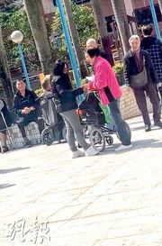 一名手持紙張、身穿黑衣的女子(左)在土瓜灣體育館票站出口外,和一名輪椅老伯交談,然後走到另一名坐輪椅的長者旁邊,同行的婆婆(紅衣者)隨即在袋中拿出一張證件交給該女子。(社總提供片段撮圖)
