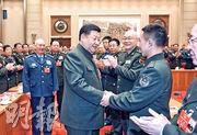 中央軍委主席習近平(前左)昨參與解放軍和武警部隊代表團審議,受到代表的鼓掌歡迎。圖為習近平與陸軍人大代表楊初格西握手。(新華社)