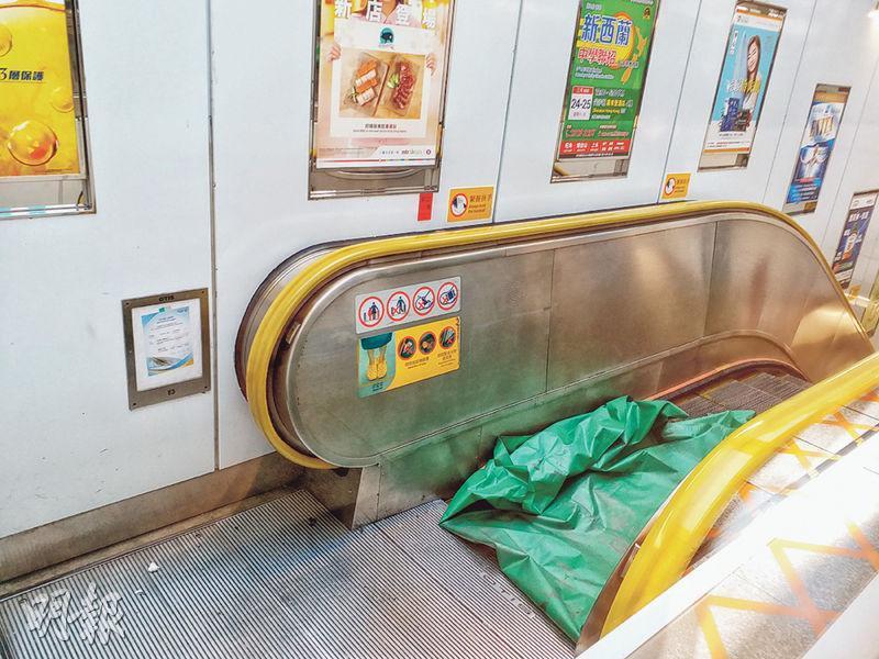 港鐵觀塘站一條上行的扶手梯發生「炒梯」意外,經初步調查相信是一條頸巾卡於梯級引致,職員事後用綠色帆布遮蓋損毁位置。(林智傑攝)