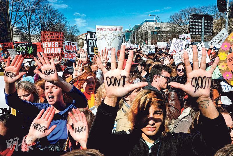 美國華盛頓前天有大規模示威,要求政府加強槍械管制,有出席者在手掌寫上「別開槍」等字句表達控訴。(路透社)
