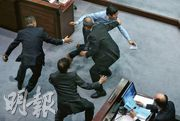 立法會議員區諾軒(上方穿恤衫者)不滿立法會一地兩檢法案委員會進入「逐條審議」階段,一度衝向官員座位(右方)理論,奔跑時更用「假身」閃避,最終被保安員攔截,雙方一同倒地。