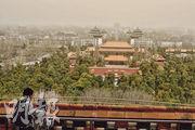 北京昨日同遭沙塵和霧霾襲擊,圖為兩名遊客在景山公園向北眺望,整個北京中軸線能見度甚低。(中新社)
