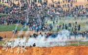 巴勒斯坦人(上方)周五在加沙南端紀念「土地日」舉行回歸大遊行,遭以色列士兵(下方)發射催彈淚乃至實彈,釀最少12死逾750人受傷。(法新社)
