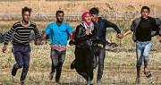 加沙巴人上周六在邊境示威期間與以軍衝突,4名巴人青年手拖手奔跑,保護一名巴人少女躲避子彈。(法新社)