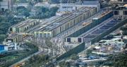 石崗車廠共有4條用作停泊高鐵列車的維修路軌,當中一條有一小段彎位。圖為石崗車廠,中間的綠色建築物為涉事車庫,可見有4組閘門供列車進出。(鄧宗弘攝)