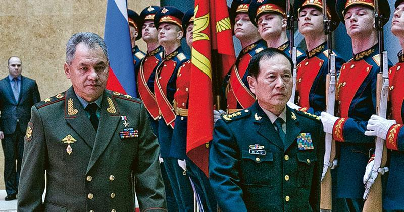 中國防長魏鳳和(右)前日在與俄國防部長紹伊古(左)舉行會談前檢閱俄軍儀仗隊。(法新社)