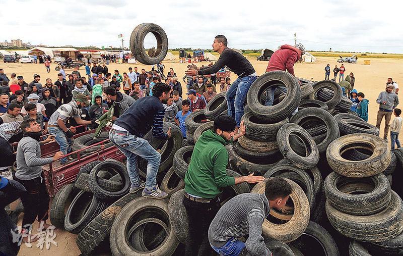 巴勒斯坦人周二在加沙地帶南部與以色列之間邊境堆放車胎,準備放火焚燒。(路透社)