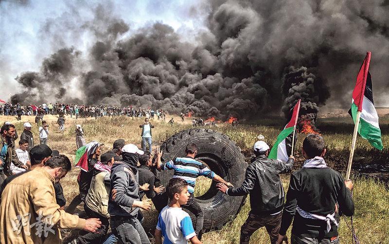 巴人示威者上周五於加沙繼續與以色列保安部隊爆發衝突,示威者焚燒車胎抗議。(法新社)