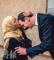 敘利亞總統府facebook周二貼出照片,顯示一名據報有親人遭杜馬市叛軍俘虜的婦人(左),在大馬士革等候消息期間親吻總統巴沙爾(右)的額頭。(法新社)