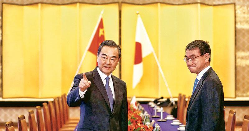 國務委員兼外交部長王毅(左)昨抵達日本訪問,並與日本外相河野太郎(右)舉行會談。(法新社)