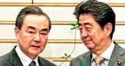 日本首相安倍晉三(右)昨日在東京與中國外長王毅(左)會晤。王毅稱,近年來兩國關係歷經波折,各領域交流合作受到影響;中日關係改善勢頭來之不易,值得珍惜。(法新社)