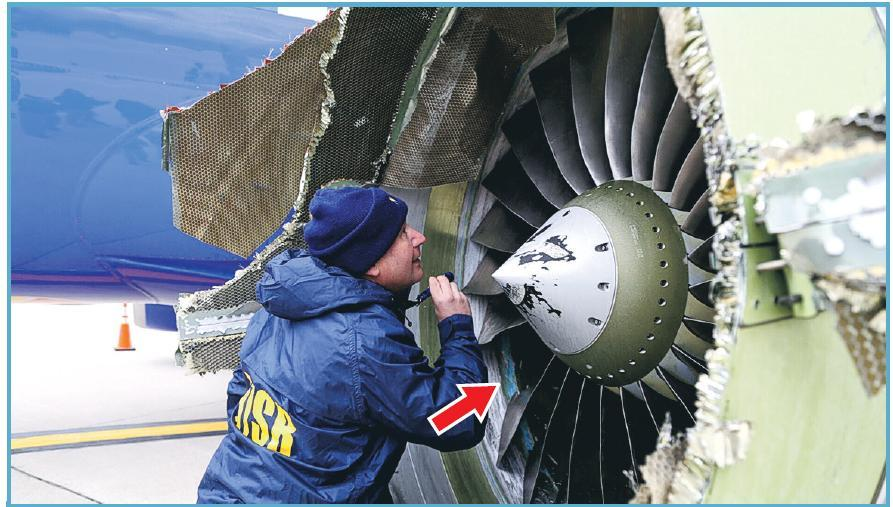 美國國家運輸安全委員會(NTSB)人員周二在費城的機場檢查肇事客機的引擎。圖中可見該引擎看來缺了一塊扇葉(箭嘴示)。(路透社)