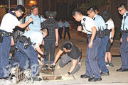 警員將被捕青年黑布蒙頭押返現場調查,其間在坑渠內檢獲懷疑涉案生果刀。(蔡方山攝)