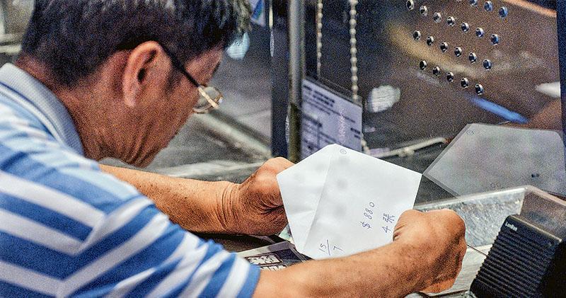 本報記者昨日觀察,在尖沙嘴香港文化中心有疑似「排隊黨」成員購買黃子華棟篤笑門票時,從白信封取出現金付款,信封面寫有「15/7  $880  4張」字眼。(明報記者攝)