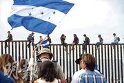 有被拒入境美國的中美洲移民,周日爬上分隔美國加州和墨西哥城鎮蒂華納的邊境圍欄上抗議。(法新社)