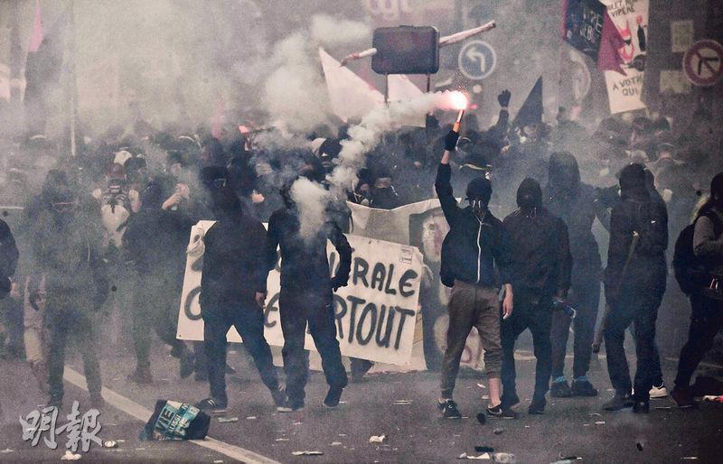 巴黎周二爆發大規模反對教育及勞工改革的示威,有黑衣人燃點火炬(圖)參與遊行。法國輿論把近日示威與1968年「五月風暴」相提並論。(法新社)