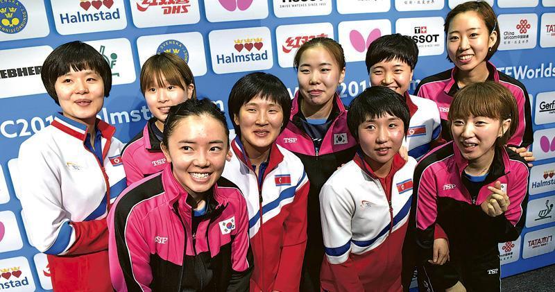 朝韓的乒乓球女隊昨宣布將組隊參加接着的4強賽事後,雙方隊伍球手親切合照,韓國選手徐孝元(前排右一)做出韓國時興的「心形」手勢。穿黑色和粉紅外套的是韓國隊員,白色及紅色外套的是朝鮮隊員,前排左一是原籍中國的韓國選手田志希。(法新社)