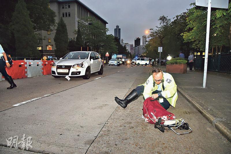 意外後,被撞老婦的個人物品如手推車、假牙等被撞至飛散路面,警員到場調查及收拾有關證物。(蔡方山攝)