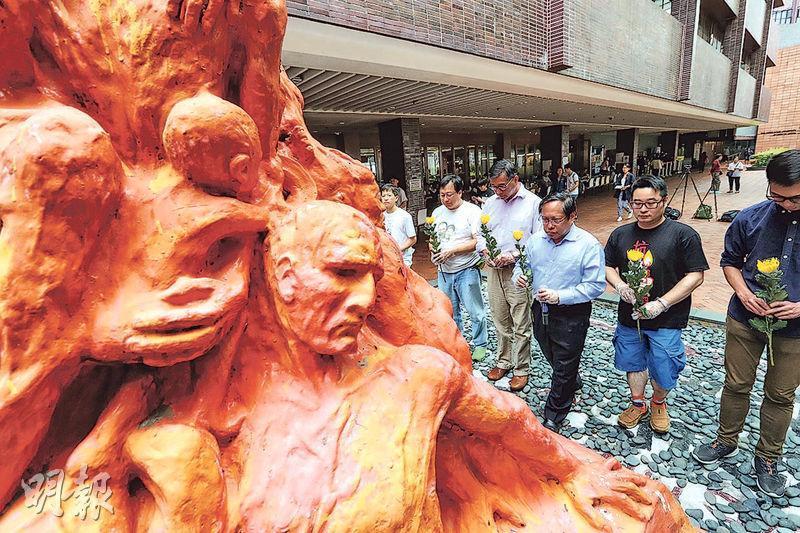 支聯會10多名成員昨日到香港大學洗刷「國殤之柱」,並為六四死難者默哀和獻花。(李紹昌攝)