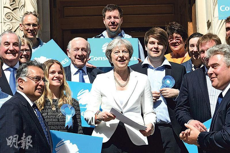 英國首相文翠珊(前右)所屬的保守黨在地選中未如之前估計般失利。圖為她昨日在保守黨繼續控制的倫敦旺茲沃思選區的市政廳外跟支持者合照。(法新社)