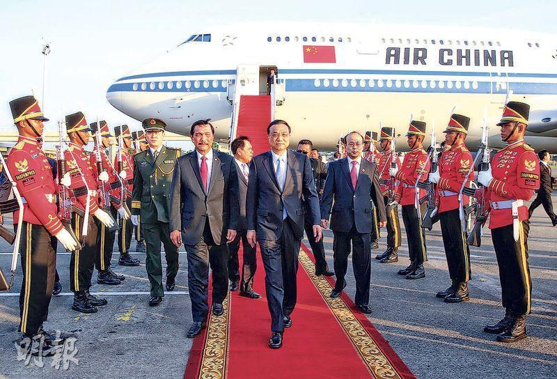 總理李克強(中)昨日下午抵達印尼訪問,印尼海洋統籌部長盧胡特(前左)到機場迎接。(中新社)