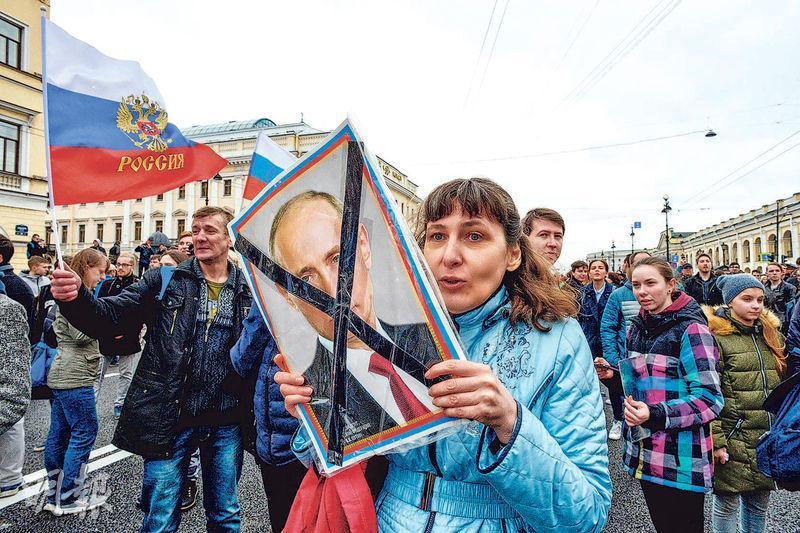 俄羅斯聖彼得堡上周六(5日)有反普京集會,一名女士拿着打交叉的普京照片參加遊行。(法新社)