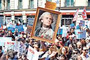 上周六巴黎有示威者舉起合成圖,將法國總統馬克龍比作18世紀被送上斷頭台的國王路易十六。(路透社)