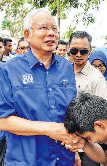 馬來西亞現首相納吉布(前左)周二到彭亨州拉票,與支持者握手。(法新社)