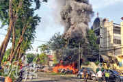 印尼泗水3間教堂昨日連環遭自殺式炸彈襲擊,造成最少13死41傷。圖為其中一間教堂門口的電單車在襲擊後起火焚燒。(路透社)