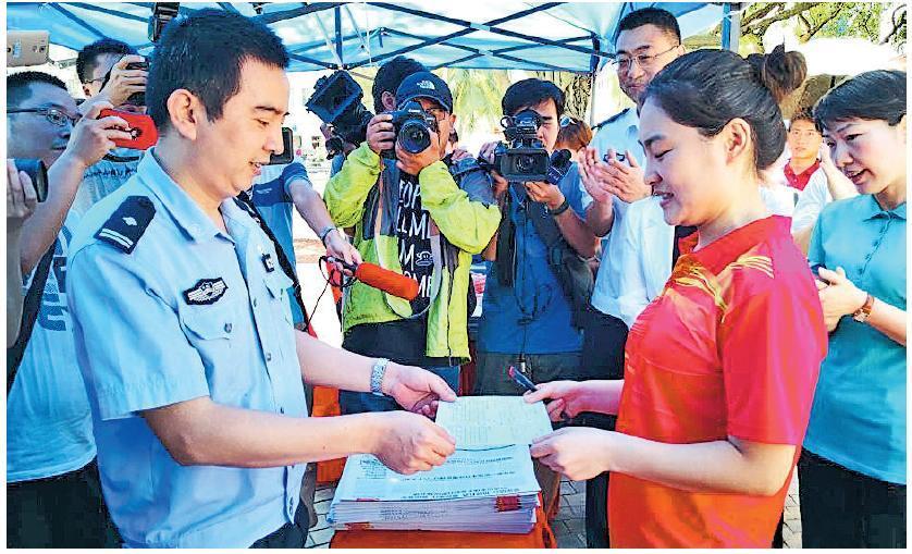海南推出《百萬人才進海南行動計劃(2018—2025年)》,海口市也發出首批落戶「綠卡」,來自吉林的鄭小姐(前右)拿到首張「准予遷入證明」。(中新社)