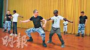 吉布提百餘名小學生昨日參觀解放軍基地。圖為小學生向軍人學習武術。(中新社)