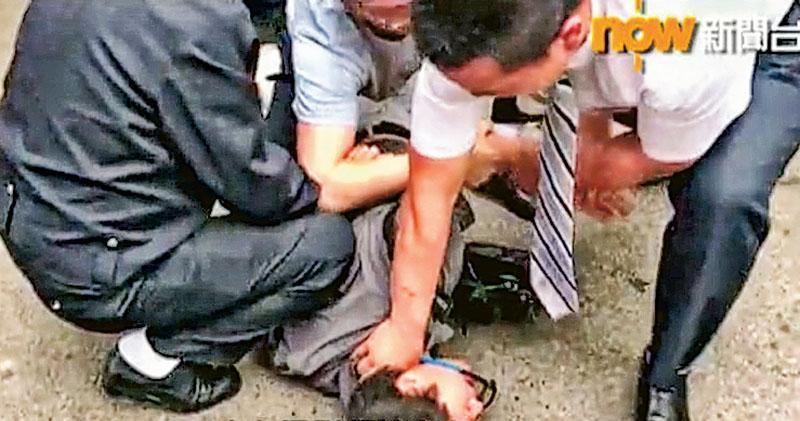 now新聞攝影師徐駿銘(灰衣者)昨早採訪北京律師協會聽證會時,遭警察阻撓及收起證件,其後被多名便衣警員按在地上鎖上手銬,致額頭流血。(now新聞截圖)