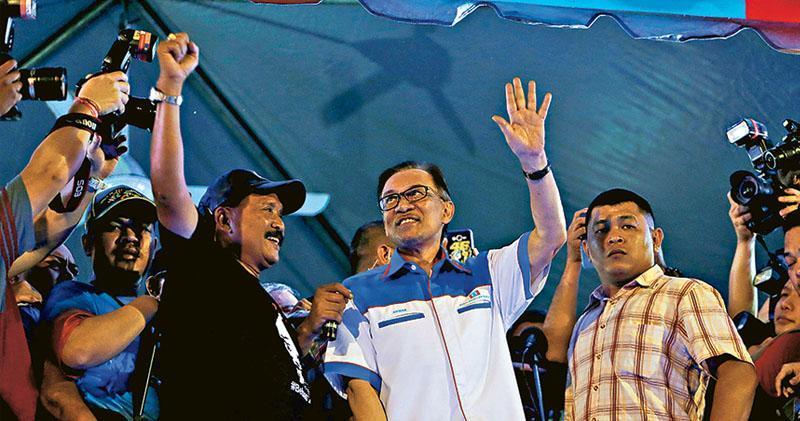 安華(中)昨晚在吉隆坡出席集會,向支持者發表講話。(路透社)