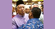 馬來西亞前首相納吉布(左)昨日前往吉隆坡國陣總部,獲支持者擁抱。(法新社)